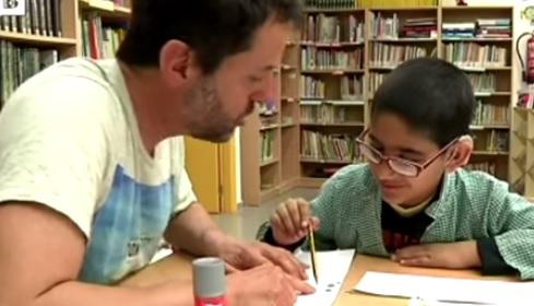 Un profesor del centro trabaja con un niño con discapacidad auditiva